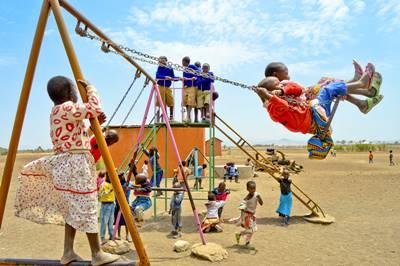 En gruppe barn leker på lekeplassen på et skoleprosjekt i Tanzania