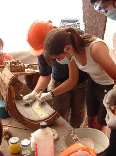 Frivillige på et arkeologiprosjekt undersøker et funn gjort under utgravninger