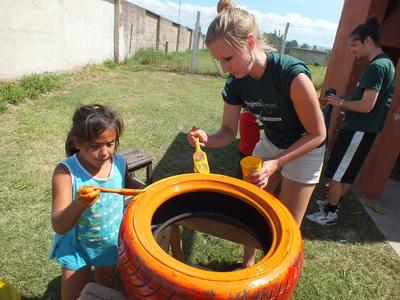 En frivillig maler et bildekk til uteområdet på et dagsenter sammen med en ung jente