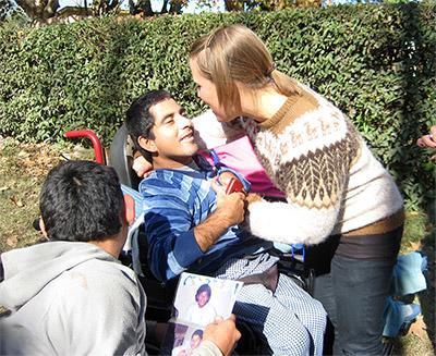 Frivillig sammen med barn i rullestol på et omsorgsenter i Argentina