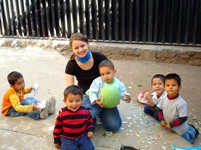 En kvinnelig frivillig sammen med små gutter på en barn- og ungdomsplassering i Belize