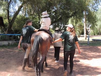 Frivillig som hjelper barn med spesielle behov på hesteterapiprosjektet i Bolivia