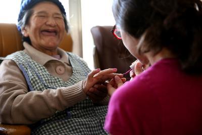En frivillig pynter en eldre kvinne på et eldresenter med neglelakk i Bolivia