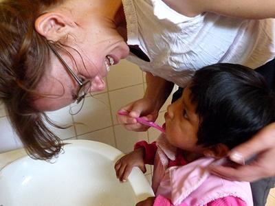 Frivillig som hjelper en liten jente med å pusse tennene i en barnehage i Bolivia