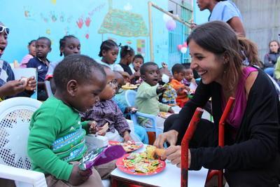 En frivillig hjelper til under et måltid i en barnehage i Etiopia