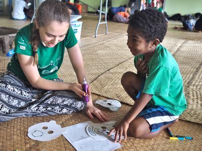 En frivillig fargelegger masker sammen med en ung gutt i en barnehage på Fiji