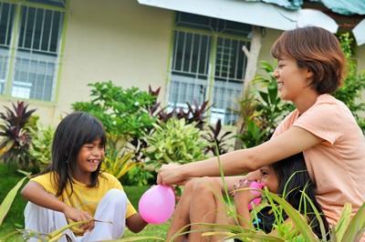 Frivillig og barn som leker med vannballonger på et omsorgsenter på barn- og ungdomprosjektet på Filippinene