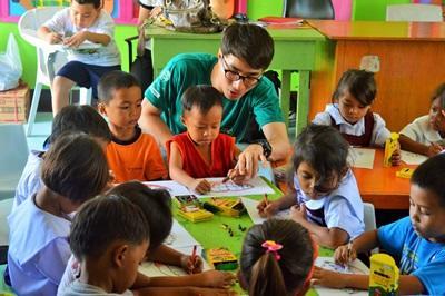 En frivillig hjelper barn med en aktivitet på et omsorgsenter på Filippinene