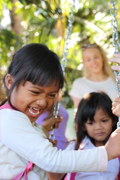 En frivillig dytter barn på en huske i en barnehage i Asia