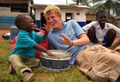 Frivillig som leker med en liten gutt på et dagsenter på barn- og ungdomprosjektet i Ghana
