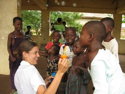 Frivillig på et barn- og ungdomprosjekt i Ghana blåser såpebobler sammen med jenter på dagsenteret