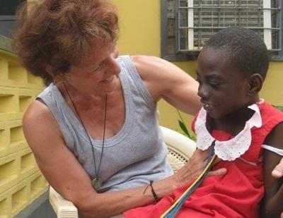 Frivillig tar seg av en jente med spesielle behov på en skole i Ghana