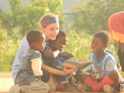 En frivillig leser sammen med en gruppe barn i Ghana