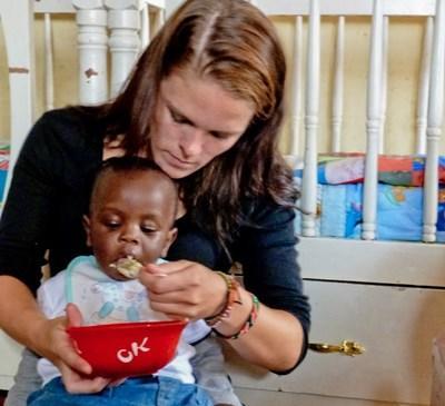 Frivillig som mater et lite barn på et dagsenter på et barn- og ungdomprosjekt i Ghana