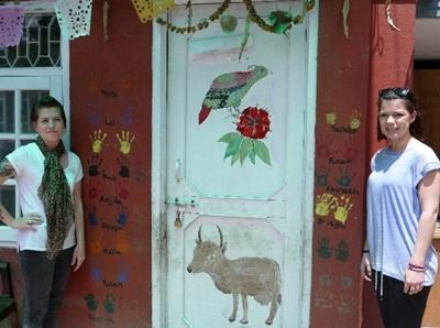 Frivillige som maler en dør i en bygning brukt av hiv/aids-prosjektet i Nepal