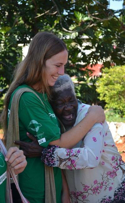 En Projects Abroad-frivillig på Barn & Ungdom-prosjekter hilser på en eldre dame på Manchester infirmary på Jamaica