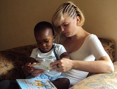 Frivillig som leser for et barn på et prosjekt på Jamaica
