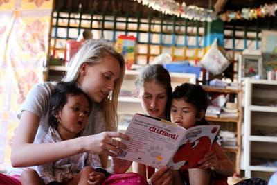 Projects Abroad-frivillige på barn & ungdom i Kambodsja leser bøker for barna på prosjektet