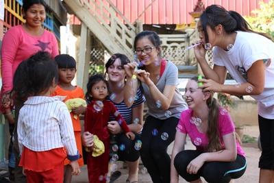 Unge Projects Abroad-frivillige blåser såpebobler med barn på barn og ungdom-prosjektet i Kambodsja Projects Abroad