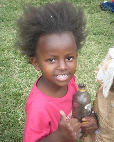 Ung gutt gir tommelen opp på et dagsenter på barn- og ungdomprosjektet i Kenya