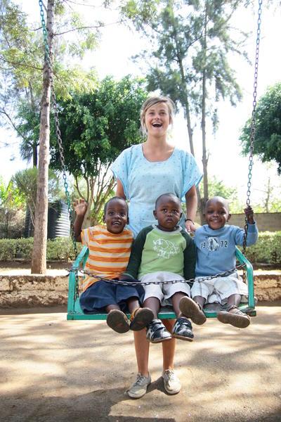 En frivillig leker med barn utenfor en barn og ungdomsplassering i Kenya
