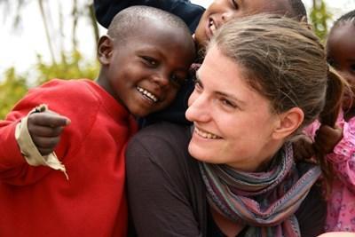Kvinnelig frivillig som smiler til kenyansk gutt i en barnehage i Kenya