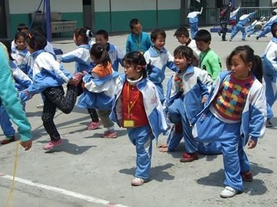 Barn som gjør uttøyninger sammen med frivillige på morgenen før dagen på dagsenteret i Kina starter