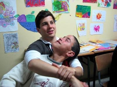 Frivillig leker med en funksjonshemmet gutt på et omsorgsenter i Marokko