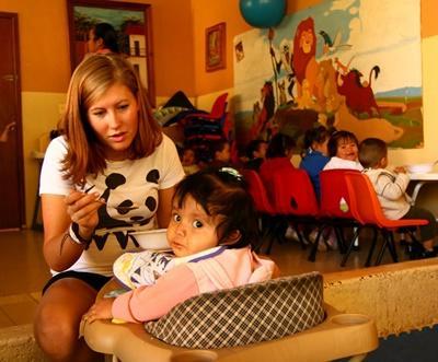 Frivillig som mater en liten jente på et omsorgsenter i Mexico