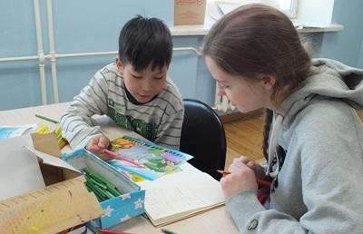 Frivillig som gjør aktiviteter med et barn på en skole på barn- og ungdomprosjektet i Mongolia