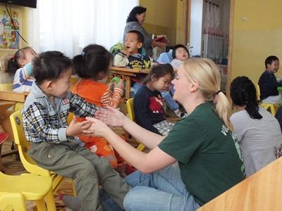 En liten gutt smiler når han leker med en frivillig på et barn- og ungdomsprosjekt i Mongolia