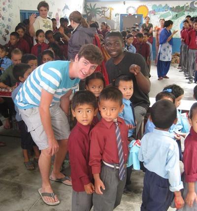 Frivillig og ansatte som aktiviserer barn på et dagsenter i Nepal
