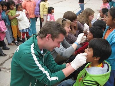Frivillig som tar en tannsjekk på barn på barn- og ungdomprosjekt i Peru