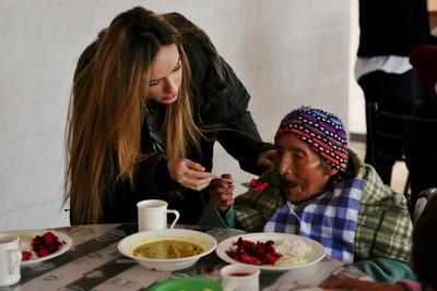 En frivillig hjelper en eldre kvinne under et måltid på eldresenter i Peru