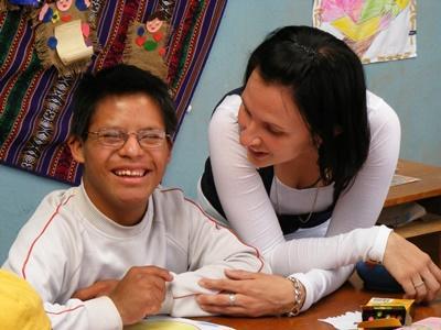 Frivillig sammen med en gutt på en skole for barn med spesielle behov i Peru