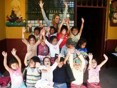 Frivillig sammen med glade barn utenfor et dagsenter i Peru