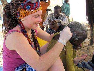 Frivillig tar en sjekk for lus på et barn på et omsorgsenter i Senegal