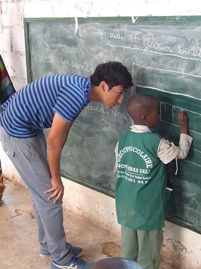 Frivillig hjelper studenter med en klasseaktivitet på tavlen i et klasserom i Senegal