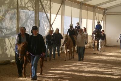 Frivillige assistere terapiryttere på ridebanen på hesteterapi-prosjejktet i Sør-Afrika