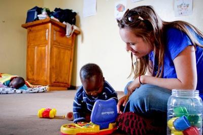 Frivillig leker med et foreldreløse barn på barn- og ungdomprosjektet i Sør-Afrika