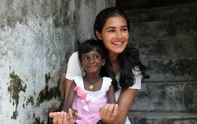 Frivillig med en liten lokal jente på et dagsenter på barn- og ungdomprosjektet