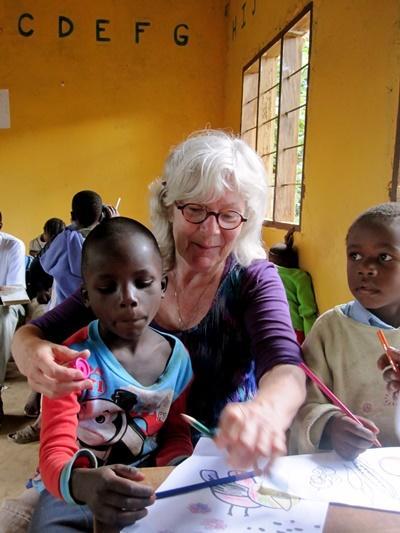 Voksne frivillig som jobber med kunst og håndverk sammen med barn på et dagsenter i Tanzania