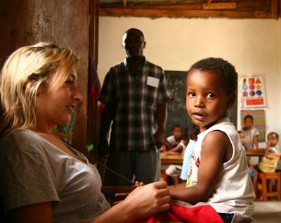 Frivillig leker med en ung gutt på et dagsenter i Tanzania