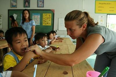 Frivillig som hjelper barn under lunsjen på et barnehjem i Thailand