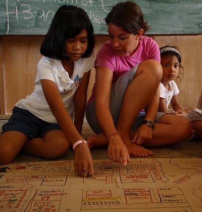 Frivillige og barn som jobber på et kunstprosjekt på et omsorgsenter i Thailand