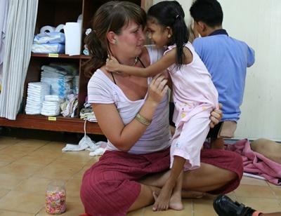 Frivillig som leker med en jente på et dagsenter på et barn- og ungdomprosjekt i Thailand
