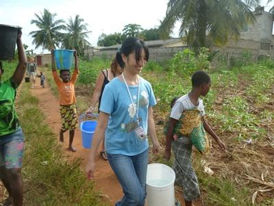 Frivillig hjelper barn med å bære bøtter med vann i Togo