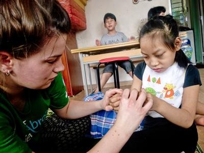 Frivillig tilbringer tid med en jente på et senter for barn med spesielle behov i Vietnam, Asia