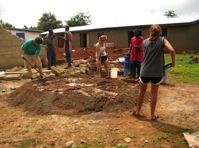 Frivillige graver en tomt for å bygge en bygning på lokalsamfunn- og byggeprosjektet i Ghana