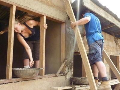 Frivillige maler en bygning på lokalsamfunn- og byggeprosjektet i Akuapem Hills i Ghana